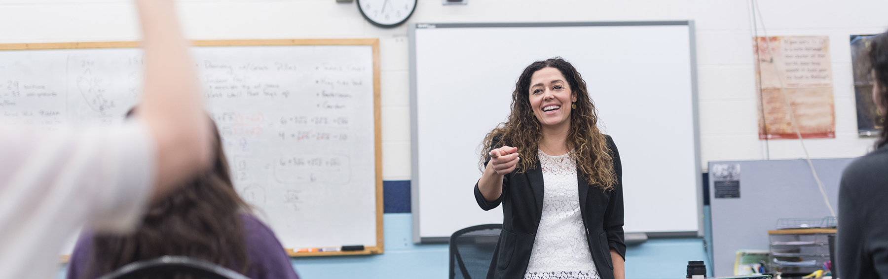 Teacher at the front of class pointing to call on student